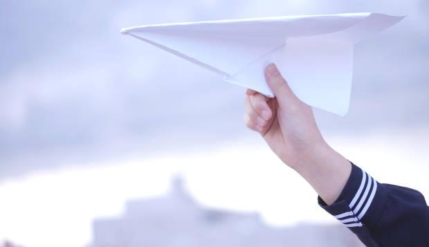 冬セーラー服の人が手にもつ紙飛行機