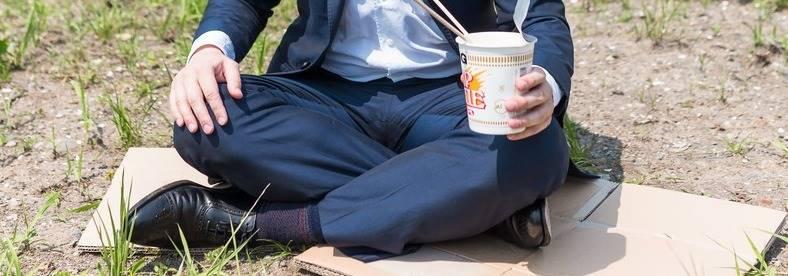 カップ麺を手にして段ボールに胡坐をかいて座る男性