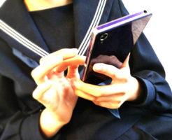 スマートフォンを手に持つ冬セーラー服の女性