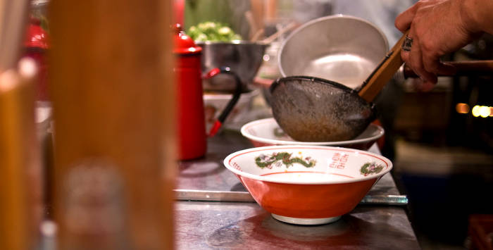 ラーメン店の丼にスープを注ぐ光景