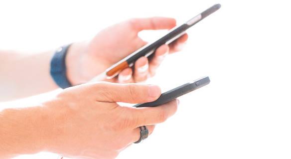 男性が両手にスマートフォンを持っている図