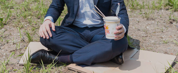 ダンボールの上でカップラーメンを食べるスーツ姿の男性