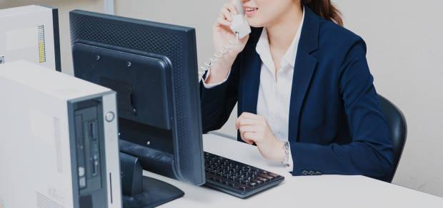 モニターの前で受話器で電話する女性